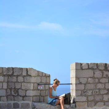 On the city wall (its a very very long city wall and this is one part of it only). Love to see fellow travellers enjoying alone time as well, so tranquil, by the sea reading. <3